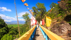 Camera Moves along Yellow Blue Bridge with Flags by Pagoda Stock Footage