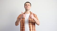 Young man showing thumbs up signs with sceptical face Stock Footage