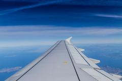 Blue horizon with soft clouds, aerial shot from airplane, with wing visible - stock photo