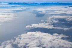 Blue sky with clouds, over landmass and sea background, aerial photography - stock photo