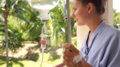 Recovering Female Patient at a Hospital Looking Outdoors Stock Footage