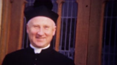 1948: Catholic deacon priest smiles in front of church windows. Stock Footage