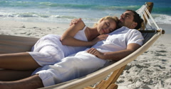 Couple relaxing in hammock at the beach Stock Footage