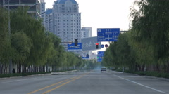 A lonely taxi drives through empty streets of suburban Ordos China Stock Footage