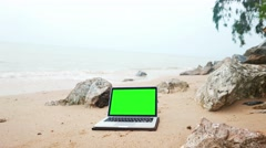 Laptop on the beach, keylight green background Stock Footage