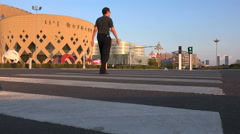 Chinese man crosses street in so called 'ghost city' Ordos Stock Footage