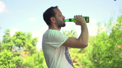 Young, happy man drinking beer in garden, super slow motion 120fps Stock Footage