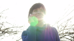 Woman smile talking on cell phone against sky light on nature outdoors - stock footage