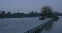 Man Freelancer Sits on a Pier With Laptop Gets up River Small Island Overgrown Stock Footage
