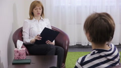 Stock Video Footage of Female psychologist making notes during psychological therapy session. sad girl
