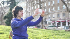 Female taking selfie picture in nature park via smartphone Stock Footage