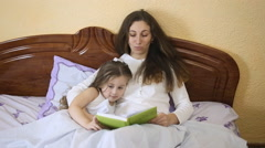Mother daughter reading a fairy tale - stock footage