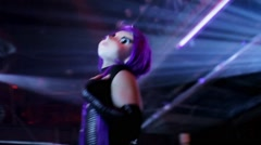 Girl dance go go in big doll head with purple hair in crowded nightclub Stock Footage