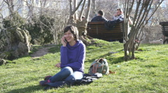 Pretty brunette woman smile talking on phone in park sitting on grass Stock Footage