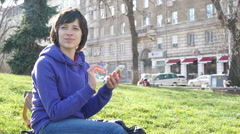 Woman type slide her smartphone chatting during sitting on grass in park Stock Footage