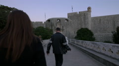 People walking on a bridge towards Bokar Fortress in Dubrovnik Stock Footage