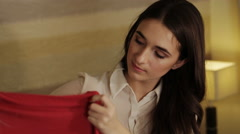 Beautiful girl sitting on the couch and folded underwear in bags Stock Footage