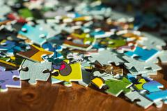 Scattered children's puzzle on a wooden table Stock Photos