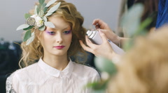 Beautiful woman doing an unusual hairstyle with fresh flowers - stock footage