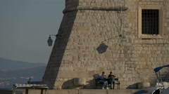 Two tourists sitting down near the City walls of Dubrovnik, Croatia Stock Footage