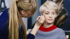 Cute girl doing makeup in the salon Stock Footage
