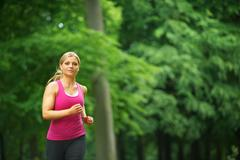 Young woman running in the park at her leisure Stock Photos