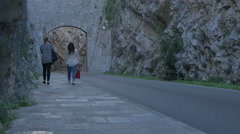 Two girls walking on a street located between mountain cliffs in Dubrovnik Stock Footage