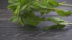 Fresh mint falling on dark wooden background Stock Footage
