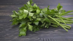 Fresh organic parsley falling on wooden background Stock Footage