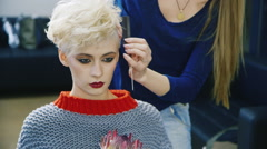 Short-haired woman doing her hair in the salon Stock Footage