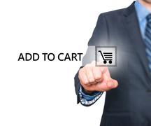 Businessman pressing add to cart button on virtual screens - stock photo