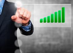 Businessman in dark suit pushing button, visual screen Growth graph going up - stock photo