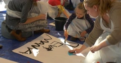 Woman Wipes the Paper Sheet Kid is Writing Words on a Paper Painting Black Kids Stock Footage