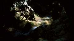 River flowing in a beam of sunlight between rocks. Stock Footage