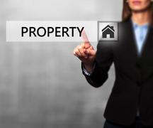 Businesswoman pressing property button on virtual screens - stock photo
