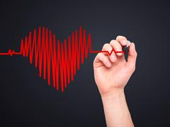 Closeup of hand drawing  heart beat in heart shape with stethoscope isolated  - stock photo