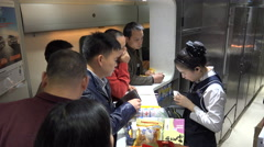 Passengers buy food from railway staff in high speed train China - stock footage