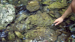 Kind boy putting back a trout into the river. Stock Footage