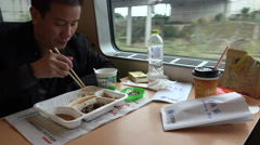 Passenger eats lunch in dining car of high speed bullet train in China Stock Footage
