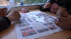 Chinese men play cards in a high speed bullet train, newspaper Stock Footage