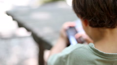 Kid playing chess with smart phone in a park. Stock Footage