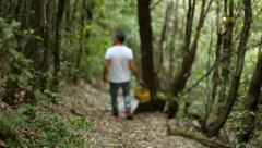 Man walking on a path with a yellow basket in his hand, Mountain wood. Stock Footage