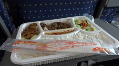A meal of rice, meat, vegetables, and pickles, on a tray table in Chinese train Stock Footage