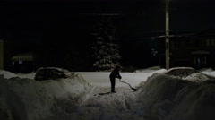 Man shovelling driveway at night after a blizzard Stock Footage