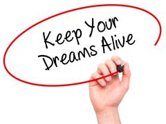 Man Hand writing Keep Your Dreams Alive with black marker on visual screen - stock photo