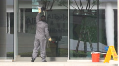 Worker cleans windows of Alibaba office building in Hangzhou, China Stock Footage