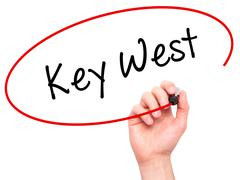 Man Hand writing Key West with black marker on visual screen Stock Photos