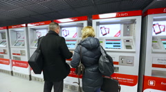 Two people are buying tickets from the ticket machine travelling airport Stock Footage