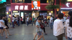 Chinese shoppers walk past popular Western KFC fast food restaurant Stock Footage