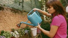 A beautiful girl watering the plants in his garden. Video about the green thumb Stock Footage